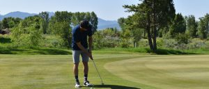 Banner image of a young man playing golf at golf course on sunny day